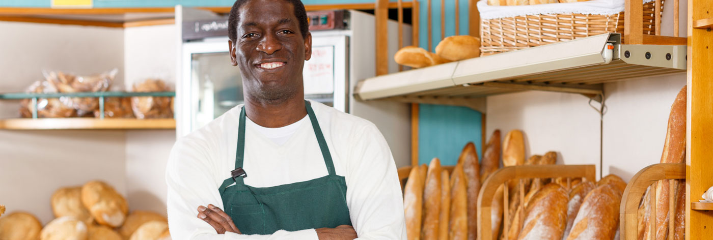 proud owner bakery shop standing arms folded behind counter fresh baked products
